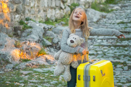 Seven-year-old girl traveler with long blond hair in a gray knitted sweater holding a teddy bear is carrying a yellow suitcase on wheels along the street of an ancient Balkan town Standard-Bild