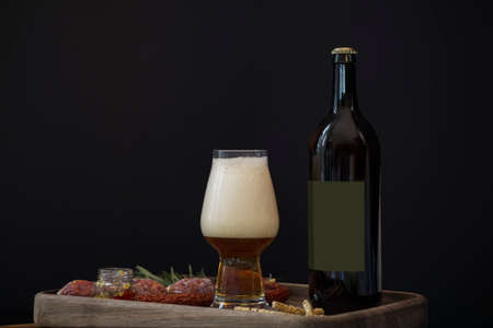 Bottle of dark beer, full beer glass with foam and snacks: hunting sausages, cheese sticks, croutons and sauce on a wooden tray