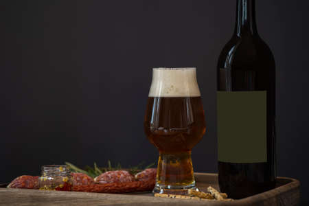 Bottle of dark beer, full beer glass with foam and snacks: hunting sausages, cheese sticks, croutons and sauce on a wooden tray close up