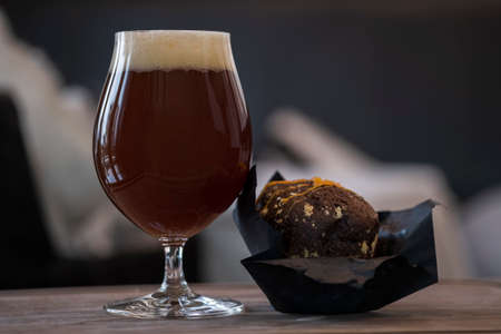 Full beer glass with cherry ale with foam cap and chocolate muffin on wooden tray close up