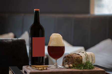 Bottle of beer, full beer glass with foam, black bread and snacks: nuts, cinnamon sticks, a sprig of rosemary on a wooden tray Standard-Bild