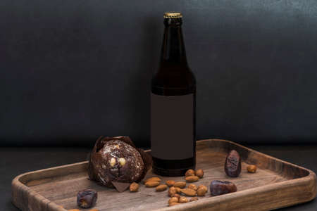 Bottle of ale, chocolate muffin and snacks: almonds and dates on a wooden tray