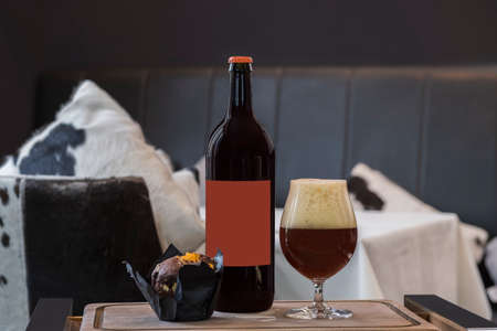 Bottle of cherry ale, full beer glass with froth, chocolate muffin on wooden tray