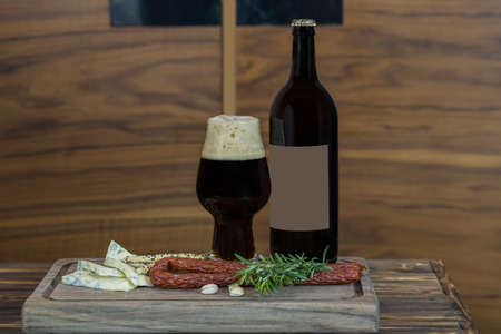 Bottle of dark beer, full beer glass with foam and snacks: hunting sausages, sliced cheese, croutons, pistachios and a sprig of rosemary on a wooden tray close-up