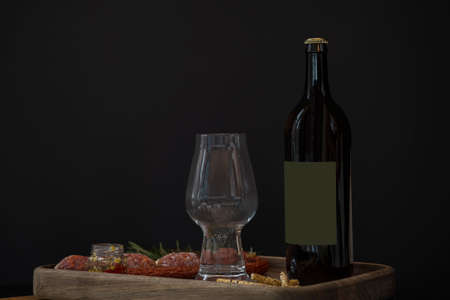 Dark beer bottle, empty beer glass and snacks: hunting sausages, cheese sticks, croutons and sauce on a wooden tray Standard-Bild