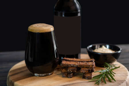 Bottle of dark beer, full beer glass with foam, black bread crackers, gravy in a saucepan, and a sprig of rosemary close-up on a wooden tray