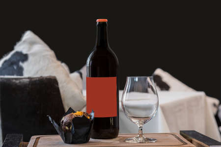 Cherry ale bottle, empty beer glass, chocolate muffin on a wooden tray