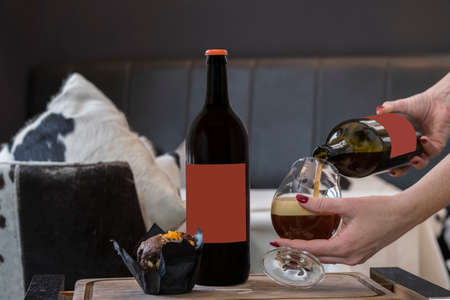 Bottle of cherry ale, chocolate muffin on a wooden tray, a female hand pours beer from a bottle into a glass Standard-Bild