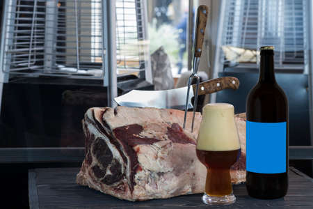 Bottle of dark beer, full beer glass with foam, large piece of raw beef meat with a knife stuck in it on the table