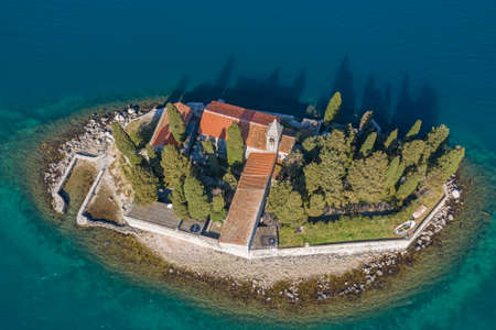 Aerial shot, drone flies above the tourquoise sea low over the small Island. On one island there is a Christian church, residential buildings and coniferous trees