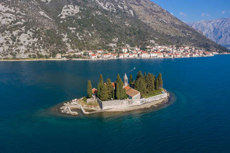 Aerial shot, drone flies above the blue sea to the small Island. On one island there is a Christian church, residential buildings and coniferous trees. Mountains and coastline are visible in the background
