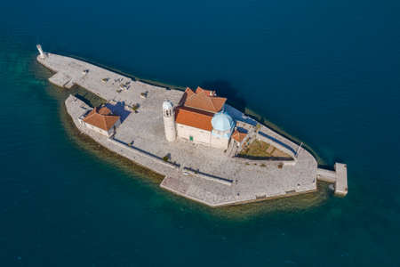 Aerial shot, drone flies above the tourquoise sea low over the small Island. On one island there is a Christian temple