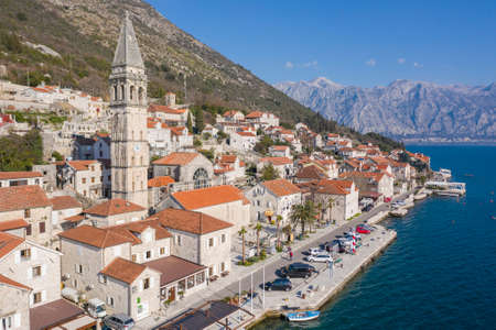 Aerial shot of the old coastal town of Perast at the foot of the mountain. Seaside promenade, residential buildings with traditional balkan red roofs, ancient Cathedral and coastline