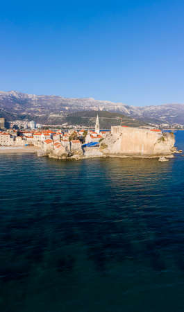 Aerial View of Budva Old Town and sandy beach in a beautiful spring day. Top view from drone on the old fortress and azure sea. Vertical panorama, Montenegro Standard-Bild