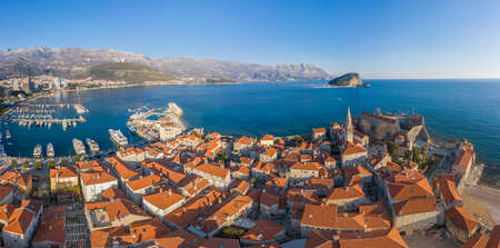 Aerial View of Budva Old Town and sandy beach in a beautiful spring day. Top view from drone on the old fortress and azure sea. Horizontal panorama, Montenegro