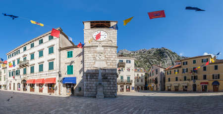 Panorama of the Old Town of Kotor, ancient square with a clock tower in the traditional Balkan architectural style with a cobblestone pavement on a sunny spring day. Mountains are visible on the backg Editorial