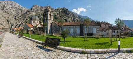 Panorama of the Old Town of Kotor, ancient buildings in the traditional Balkan architectural style with a cobblestone pavement on a sunny spring day. Mountain with ruines of ancient fortress