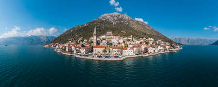 Panorama bird's eye view of small island in Adriatic sea, covered by greenery, traditional Balkan style architecture, ancient buildings and cathedral. Mountains in the background