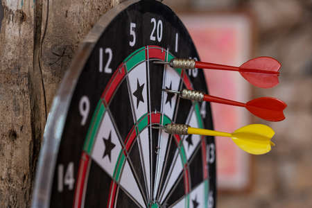 Photo of a dart board with three darts arrows. Dart arrows hit on bull eyes of dartboard. The arrows didn't hit the bull's-eye, but they hit the top ten. Target and goal as concept