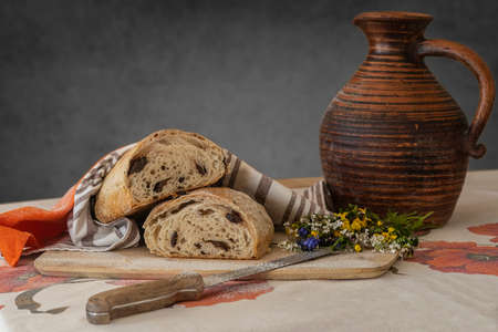 Still life, food photography - close-up of fresh sliced white bread on a cutting board on the table, knife, linen towel and little bouquet of wildflowers, a jug of milk in the background