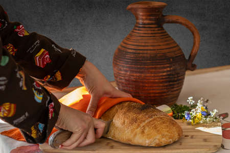 Food photography - woman's hand cuts bread with a long knife on a cutting board. In the background are a clay jug of milk and a bouquet of wildflowers