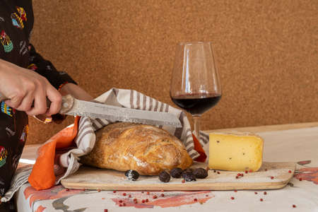 Food photography - woman's hands are holding a knife and cut a loaf of freshly baked white bread. There is a piece of cheese on the cutting board, next to it there is a glass of red wine. Wooden table Stok Fotoğraf