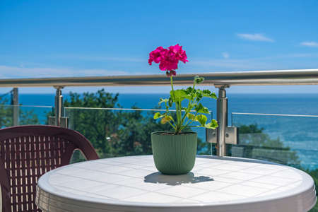 View on the azure sea and blue sky from the private villa's terrace. On the terrace there is a plastic table with a chair, on the table there is a red flower for decoration