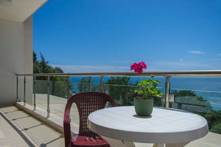 Spacious terrace in the private villa with sea view. The terrace offers view on the sea and coastline, covered by greenery. On the terrace there is a plastic table with a chair, on the table there is a red flower for decoration