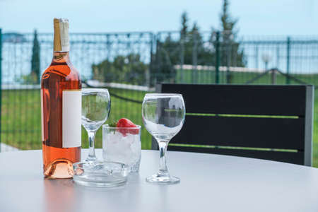 Served table on the terrace of a luxury villa. On the table are a bottle of rose wine, two empty glasses and an iced strawberry. View from the terrace to the green lawn and the sea in the distance Stok Fotoğraf