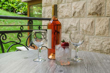Served table on the terrace of a luxury villa. On the table are a bottle of rose wine, two empty glasses and an iced strawberry. Garden view from the terrace