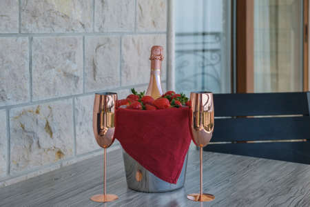 Served table on the terrace of a luxury villa. On the table are a bucket with champagne, strawberries and two empty glasses.