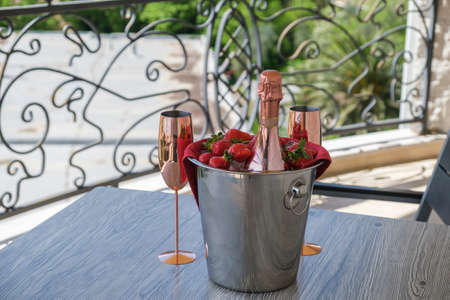 Served table on the terrace of a luxury villa. On the table are a bucket with champagne, strawberries and two empty glasses. Garden view from the terrace