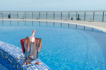 Swimming pool view. Close-up of a bucket with champagne, strawberries and two empty glasses on the side of the pool Stok Fotoğraf