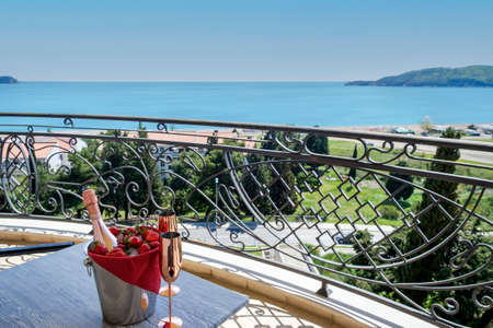 Served table on the terrace of a luxury villa with sea view. On the table are a bucket with champagne, strawberries and two empty glasses. Through the balcony lattice we see the blue sky and the azure sea Stok Fotoğraf