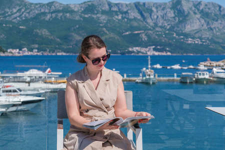 Young pretty European woman in sunglasses with long brown hair pulled back is sitting at a terrace of a summer cafe with sea and marina view and reading a magazine