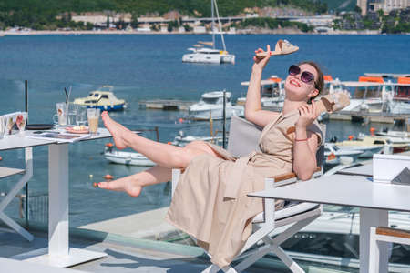Young pretty European woman on vacations resting and having fun in a cafe terrace with sea view, holding her sandals in the hand. Humor, having fun on vacations concept