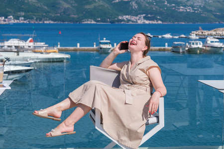Young pretty European woman on vacations resting and having fun in a cafe terrace with sea view, talking on her smartphone and laughing. Humor, having fun on vacations concept