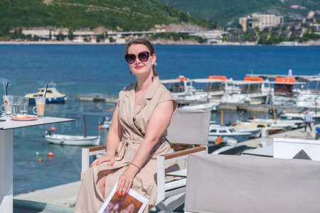 Young pretty European woman in sunglasses with brown hair pulled back is sitting at in a terrace of a summer cafe with sea and marina view and holds a magazine, smiling Stok Fotoğraf