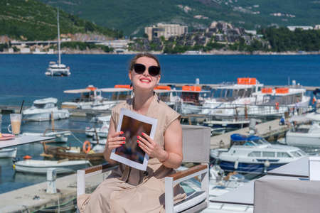 Young pretty European woman in sunglasses with brown hair pulled back is sitting at in a terrace of a summer cafe with sea and marina view and holds a magazine, laughing