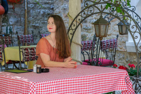 Young pretty European woman with long brown hair is sitting at a table in a courtyard of summer cafe, smiling, and waits for her order