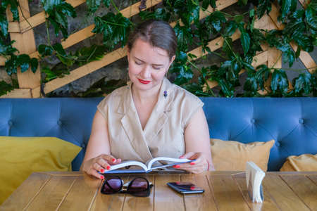 Young pretty European woman with long brown hair pulled back in a ponytail is sitting at a table in a terrace of a summer cafe and reading a book Stok Fotoğraf