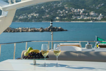 Yacht cruise. A table is set on the deck, there are glasses of white wine and a dish of fruit on the table. The yacht offers a view of the lighthouse and the mountains Stok Fotoğraf