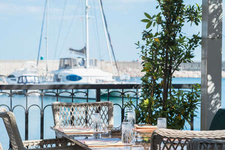 Outdoor cafe tables on the seaside embankment of mediterranean town in a summer day. Cafe offers a sea and marina view with yachts Stok Fotoğraf