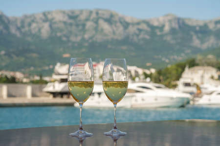 Yacht cruise. A table is set on the deck, there are two glasses of white wine on the table. The deck of the yacht offers view of the marina and mountains Stok Fotoğraf