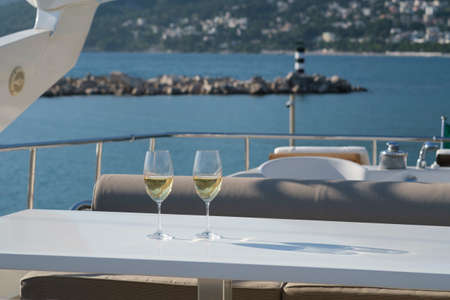 Yacht cruise. A table is set on the deck, there are two glasses of white wine on the table. The deck of the yacht offers view of the lighthouse, marina and mountains