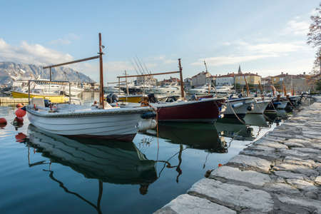 Budva, Montenegro, February 05, 2021: View of marina of the montenegrin town Budva. Motor boats, boats and yachts moored at the pier in the port. Old town center is visible on the background