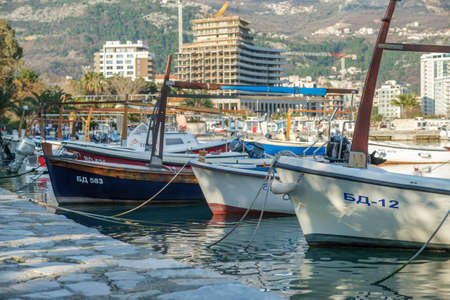 Budva, Montenegro, February 05, 2021: View of marina of the montenegrin town Budva. Motor boats, boats and yachts moored at the pier in the port. Residential building and mountains are visible on the background
