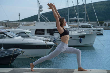 Young slim beautiful woman practicing yoga in the marina, against the background of yachts standing at the pier. Exercising, making yoga pose on the seashore Stok Fotoğraf