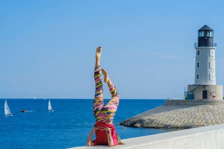 Young slim beautiful woman practicing yoga on the seashore, in the marina, against the background of the sea and lighthouse. Exercising, making yoga pose on the seashore