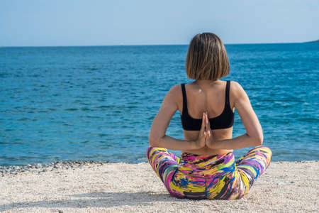 Young slim beautiful woman practicing yoga on the seashore, on the beach, against the background of the sea. Exercising, making yoga pose on the sandy beach. Back view Stok Fotoğraf